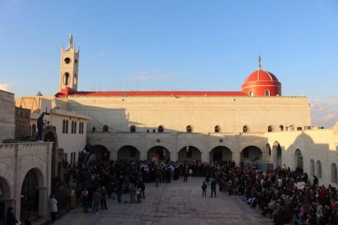pandemic terror threats iraq papal trip is complicated even for francis  Crowds surround Cardinal Pietro Parolin, Vatican secretary of state, Dec. 28, 2018, as he visits the Syriac Catholic cathedral, St. Mary al-Tahira, in Qaraqosh, a city in the Ninevah Plains, where some 100,000 Christians were uprooted in 2014 by Islamic State fighters. (CNS/Vatican Media)